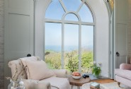 The floor-length arched window in the sitting room with dramatic sea views
