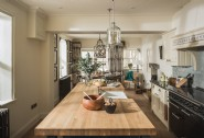 The luxury kitchen boasts a Falcon range and log burner for cosy family suppers