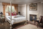 Double bedroom with feature fireplace and original mullion windows
