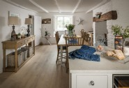The open plan kitchen and dining room features an electric woodburner