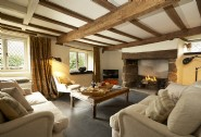 Exposed beams and open fire in the luxury living room