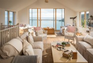 The light-filled living areas are flooded with blue hues from the sea