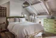 The king-size handcrafted bed in the rafters of Little Portion