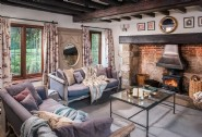 In the living room of Roserai, sofas face the wide inglenook fireplace