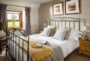 The master bedroom at Seapink Cottage enjoys garden views