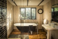 Spacious bathroom with claw-foot roll-top bath tub and double shower