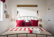 The king-size cast iron bed dressed with plump pillows in pillar box red