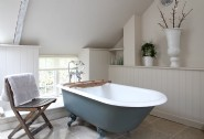 A clawfoot bath adds charm to this luxury en suite bathroom off the twin bedroom