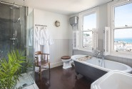 The family bathroom is complete with a bathtub and separate shower