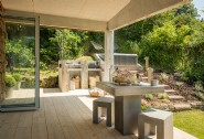 The covered deck features a handcrafted concrete barbecue