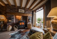Cosy lounge, exposed oak beams and glowing wood burner