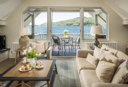 The open-plan living room opens out onto the elevated deck above Lake Windermere