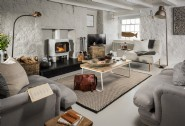 The soft grey tones and fresh white walls complement the original beams