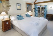 The master en suite bedroom with French doors leading out to the decking