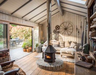 Rustic sitting room with central round wood-burner