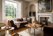The large lounge with huge windows and cosy log burner