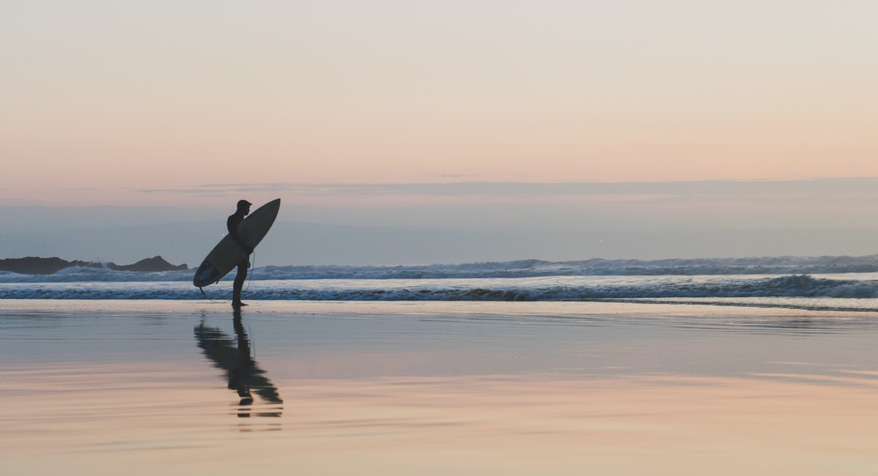 Solitary Surfer on a Calm Beach | Coastal Retreats